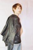 Mujer joven atractiva en chaqueta de cuero negra en el fondo blanco Imagen de archivo