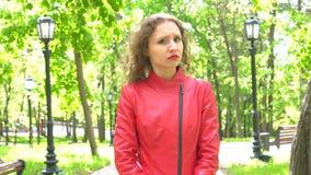 Mujer joven atractiva en chaqueta roja que dice no sacudiendo la cabeza al aire libre metrajes