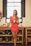 Mujer joven atractiva en cocina con una taza de café Fotos de archivo