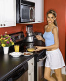 Mujer joven atractiva en cocina que cocina Breakfas Foto de archivo libre de regalías