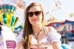 Mujer joven atractiva en el funfair alemán Oktoberfest con el vestido tradicional del dirndl Fotos de archivo