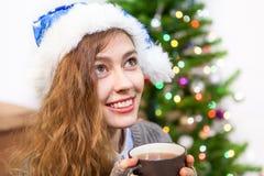 Mujer joven atractiva en el sombrero azul de Papá Noel que sostiene la taza caliente del té en manos Foto de archivo