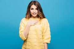 Mujer joven atractiva en el suéter amarillo que presenta en fondo azul Fotografía de archivo libre de regalías