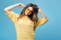 Mujer joven atractiva en el suéter amarillo que presenta en fondo azul Muchacha bonita en vidrios amarillos Foto de archivo libre de regalías