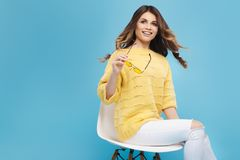 Mujer joven atractiva en el suéter amarillo que presenta en fondo azul Muchacha bonita en vidrios amarillos Imagen de archivo libre de regalías