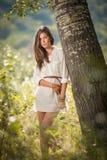 Mujer joven atractiva en el vestido del cortocircuito del blanco que presenta cerca de un árbol en un día de verano soleado Mucha Imágenes de archivo libres de regalías