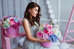 Mujer joven atractiva en el vestido elegante que se sienta en el interior del estudio adornado con las flores Muchacha sonriente  Imágenes de archivo libres de regalías