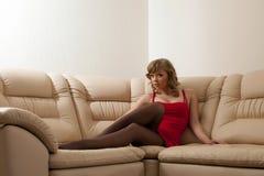 Mujer joven atractiva en la alineada roja que se sienta en el sofá Foto de archivo