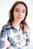 Mujer joven atractiva en la camisa de tela escocesa que se coloca con las manos dobladas Fotos de archivo libres de regalías