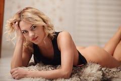 Mujer joven atractiva en la lencería sexy que presenta cerca de una cama Imagen de archivo libre de regalías