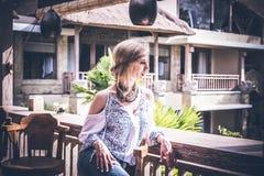 Mujer joven atractiva en la mirada étnica del estilo que presenta en el restaurante tropical, retrato Isla tropical Bali, centro  imagen de archivo