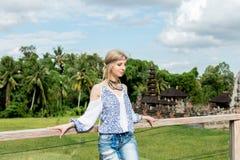 Mujer joven atractiva en la mirada étnica que presenta cerca del templo del balinese, retrato del estilo Isla tropical Bali, lujo Foto de archivo