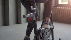 Mujer joven atractiva en la ropa de deportes negra que completa un ciclo en gimnasio y que escucha la música de los auriculares metrajes