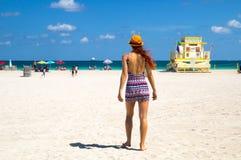 Mujer joven atractiva en mini vestido elegante que camina hacia Océano Atlántico en Miami Beach, la Florida, con la torre del sal imagenes de archivo