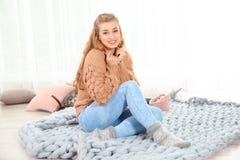 Mujer joven atractiva en sentarse caliente acogedor del suéter fotos de archivo