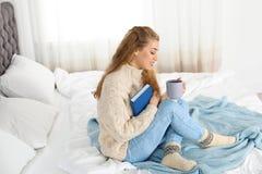 Mujer joven atractiva en suéter caliente acogedor con la taza de bebida caliente y el libro que se sienta en cama foto de archivo
