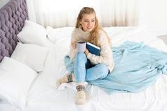 Mujer joven atractiva en suéter caliente acogedor con la taza de bebida caliente y el libro que se sienta en cama imagen de archivo
