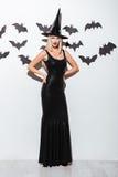 Mujer joven atractiva en traje negro de la bruja con el sombrero Imágenes de archivo libres de regalías