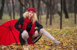 Mujer joven atractiva en un lanzamiento de la moda del otoño. Chica joven de moda hermosa con los accesorios rojos al aire libre Fotos de archivo libres de regalías