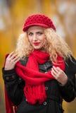 Mujer joven atractiva en un lanzamiento de la moda del otoño. Chica joven de moda hermosa con los accesorios rojos al aire libre Foto de archivo