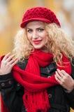 Mujer joven atractiva en un lanzamiento de la moda del otoño. Chica joven de moda hermosa con los accesorios rojos al aire libre Imagen de archivo