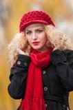 Mujer joven atractiva en un lanzamiento de la moda del otoño. Chica joven de moda hermosa con los accesorios rojos al aire libre Fotografía de archivo
