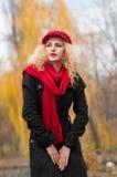 Mujer joven atractiva en un lanzamiento de la moda del otoño. Chica joven de moda hermosa con los accesorios rojos al aire libre Foto de archivo libre de regalías