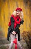 Mujer joven atractiva en un lanzamiento de la moda del otoño. Chica joven de moda hermosa con los accesorios rojos al aire libre Imagenes de archivo