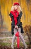 Mujer joven atractiva en un lanzamiento de la moda del otoño. Chica joven de moda hermosa con los accesorios rojos al aire libre Imagen de archivo libre de regalías