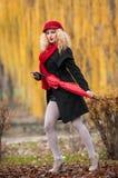 Mujer joven atractiva en un lanzamiento de la moda del otoño. Chica joven de moda hermosa con los accesorios rojos al aire libre Fotografía de archivo libre de regalías