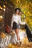 Mujer joven atractiva en un tiro otoñal al aire libre Colegiala de moda hermosa que presenta en parque con las hojas descoloradas Foto de archivo libre de regalías