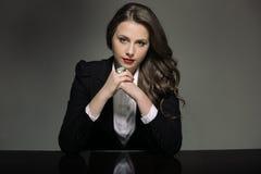 Mujer joven atractiva en un traje negro que se sienta en la tabla Foto de archivo