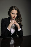 Mujer joven atractiva en un traje negro que se sienta en la tabla Fotos de archivo