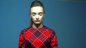 Mujer joven atractiva en vestido rojo en el estudio que lanza en la cámara al paquete de dinero en la cámara lenta metrajes