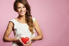 Mujer joven atractiva en vestido rosado con el corazón en Valentine Day en fondo rosado Fotos de archivo libres de regalías