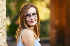 Mujer joven atractiva feliz alegre treinta años con los vidrios en la calle en verano Fotos de archivo