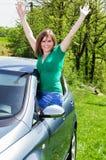 Mujer joven atractiva feliz fuera de agitar de la ventanilla del coche fotos de archivo libres de regalías