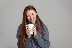 Mujer joven atractiva feliz que lleva a cabo la taza blanca y la risa Imagen de archivo libre de regalías