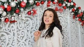 Mujer joven atractiva feliz que toca las bolas blancas y rojas de la Navidad en estudio adornado y la sonrisa metrajes