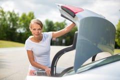 Mujer joven, atractiva, feliz que toma una maleta de su coche Fotos de archivo libres de regalías