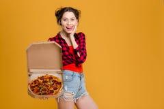 Mujer joven atractiva graciosamente que muestra la lengua y que sostiene la pizza Imágenes de archivo libres de regalías
