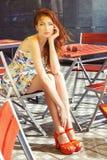 Mujer joven atractiva hermosa con el pelo rojo largo que se sienta en un café en la calle en la ciudad después de una lluvia y qu Fotos de archivo