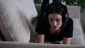 Mujer joven atractiva hermosa con el smartphone que miente en el sofá y que escucha la música almacen de video