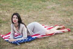 Mujer joven atractiva hermosa con el vestido clásico que se acuesta en bandera americana en el parque modelo de moda que lleva a  imagenes de archivo