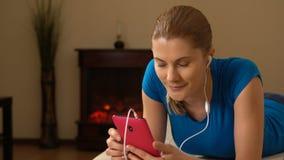 Mujer joven atractiva hermosa con un smartphone que miente en un sofá y que escucha la música almacen de video