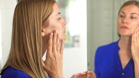 Mujer joven atractiva hermosa en blusa azul marino que comprueba su cara en espejo en cuarto de baño almacen de metraje de vídeo