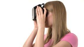 Mujer joven atractiva hermosa en camiseta rosada usando sus vidrios de VR Fondo blanco aislado almacen de video