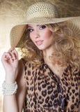 Mujer joven atractiva hermosa en maquillaje brillante del leopardo del vestido en el estudio en un fondo del oro en el sombrero Imagen de archivo libre de regalías