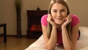 Mujer joven atractiva hermosa en una camiseta rosada que miente en un sofá y que sonríe en la cámara almacen de metraje de vídeo