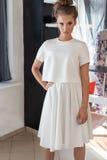 Mujer joven atractiva hermosa en vestido blanco de moda hermoso en el estudio que presenta para el lanzamiento de la moda de la c Imagen de archivo libre de regalías